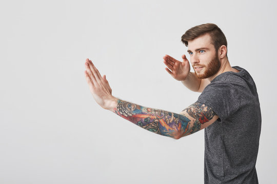 Beautiful cool european bearded man with tattoo and good-looking hairstyle looking aside having concentrated expression, gesticulating with hands showing his karate poses.
