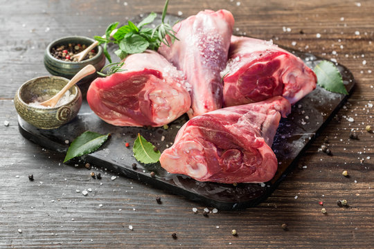 Raw lamb shanks with salt and pepper on stone tray on rustic wooden table. selective focus