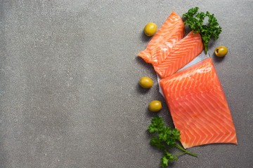 Fillet of red fish on a gray background with greens and olives. View from above