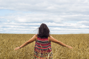 young brunette girl standing on wheat field and enjoying nature