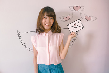 A young asian model with angel wings holding a love mail letter with flying hearts at the background