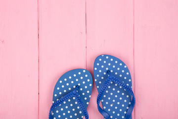 Blue flip flops in polka dots on pink wooden background