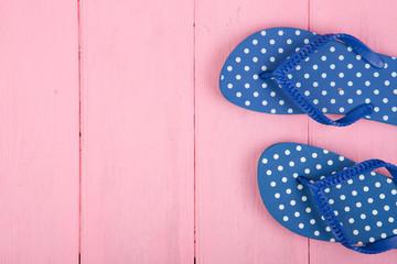 Blue flip flops in polka dots on pink wooden background