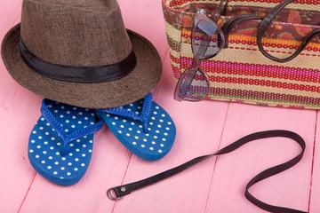 Summer accessories - sunglasses, straw beach bag, sun hat, belt and flip flops on pink wooden table