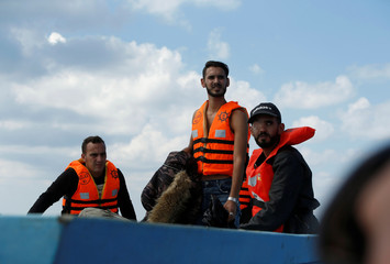 Libyan migrants on a wooden boat await rescue by the migrant search and rescue vessel MV Seefuchs of the German NGO Sea-Eye south of the Al Jurf Oilfield some 45 nautical miles off the coast of Libya