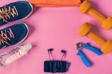 Sports accessories on a pink background. Sneakers, bottle of water, dumbbell, smartphone and earphones. Copy space