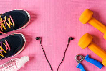 Sports accessories on a pink background. Sneakers, bottle of water, dumbbell, earphones. The place for the text.