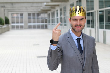 Happy businessman with a crown in office space