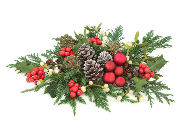 Christmas decorative display red bauble decorations, holly, ivy, mistletoe, cedar and juniper leaf sprigs and pine cones on white background.