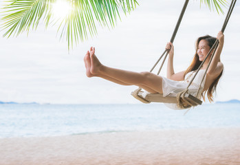 Wall Mural - Asian lady relax and fun with swing under coconut leaves and sand beach