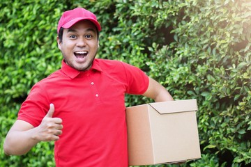 Smiling young male postal delivery courier man in beside of cargo van delivering package.Impressive service.