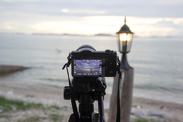 The camera is taking a picture of the sea, the lamp, the sunset at sunset.
