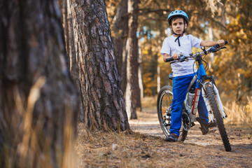 kid on a bicycle in the sunny forest. boy cycling outdoors in helmet