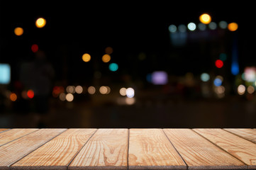 empty wood table in front of blurred montage night market bokeh background