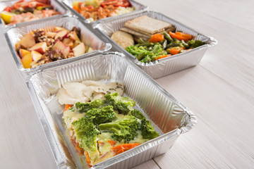 Healthy food take away in foil boxes on wood background