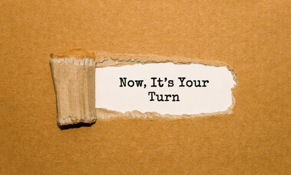 The text Now, Its Your Turn appearing behind torn brown paper