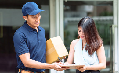 Smiling Asian delivery man holding a cardboard box while beautiful Asian woman putting signature in clipboard to receive package