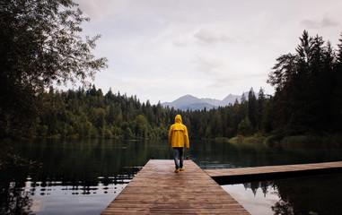Man standing on the lake walkway