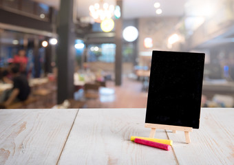 Blank restaurant blackboard on easel with blurred bokeh restaurant background,text space