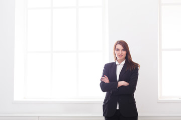 Successful, beautiful businesswoman in official suit standing in white office interior