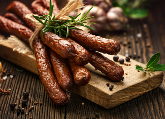 Kabanosy, polish sausages made of pork on a board with addition of fresh herbs and spices