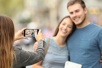Friends taking photos with a smart phone on the street