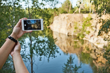 view of a girl taking a picture of a canyon on her smartphone