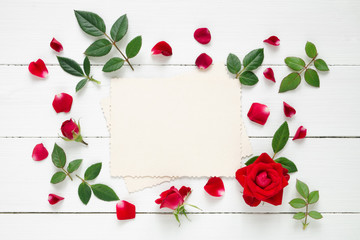 Retro empty photo frame for the inside and red rose flowers on white background. Flat lay, top view.