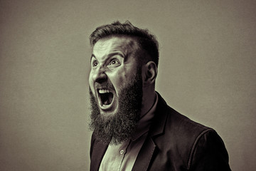 Concept of anger. Bearded man in suit shouts in a state of anger. Black and white image in vintage style.