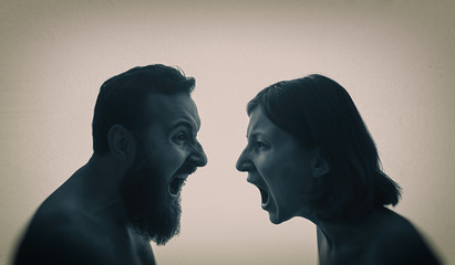 A man and a woman scream at each other. The concept of a family quarrel, violence, misunderstanding.