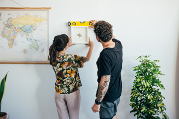 View of cute romantic young hipster couple, just moved in into new apartment studio or flat, hang painting or frame using level tool instrument to measure height