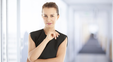 Smiling young female. Casual businesswoman standing at the office.