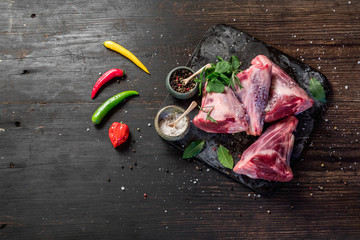 Raw lamb shanks with salt and pepper on stone tray on rustic wooden table, selective focus