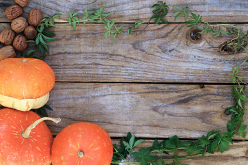 Autumnal background with pumpkins and nuts on old wooden table