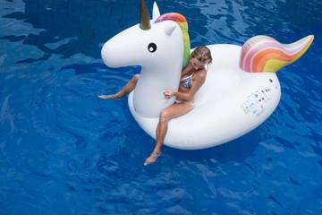 Top view of woman in bikini sitting on the big white inflatable unicorn in the pool