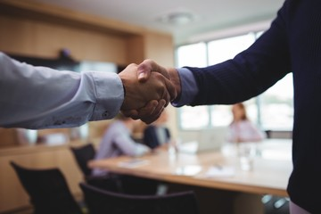 Business people shaking hands during meeting in board room