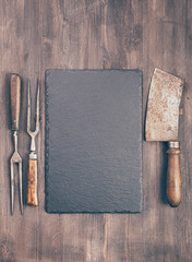 Slate coaster with vintage meat cleaver and fork on wooden background with copy space