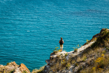 Young man turned back to the camera with backpack standing and looking at distance with the blue sea in front, relaxed, concept of freedom. Vacation.