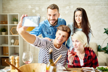 Portrait of happy friends taking selfie at dinner table while celebrating festive occasion