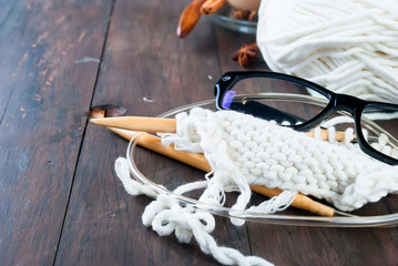 Cup of tea with milk , knitting threads and glasses  on a wooden table.