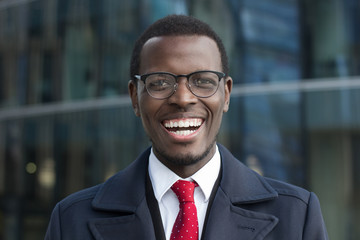 Close up portrait of successful confident african american corporate executive business man. Happy smiling black businessman standing against office building.