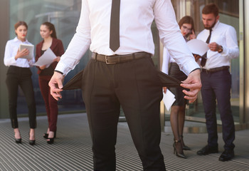 A young man with his pockets turned out against the backdrop of the office. bankruptcy, poverty