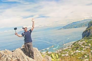 man taking selfie on mountain top overlooking small coastal city