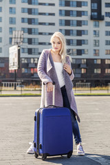 A young woman came with a suitcase on a business trip. The concept of travel, work, lifestyle.