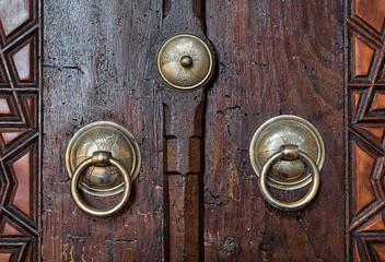 Closeup of two antique copper ornate door knockers over an aged wooden door