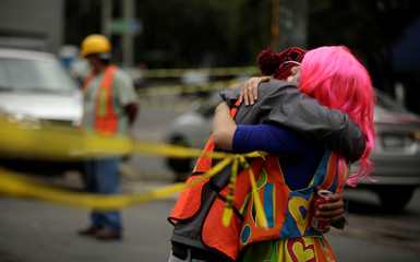 A woman embraces a member of the rescue team outside a collapsed building after an earthquake in Mexico City