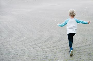Little child running away. Back view.