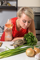 Girl mops surprised on tortoise who is eating salad