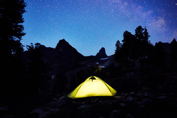 Glowing tent in the background of the night starry sky in the mountains. Thousands of stars in the night sky. Tourists rest in a tent under a billion stars