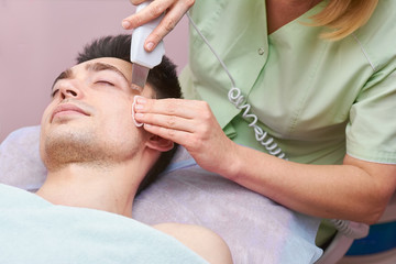 Hands using ultrasonic face scrubber. Cosmetologist working with young man.